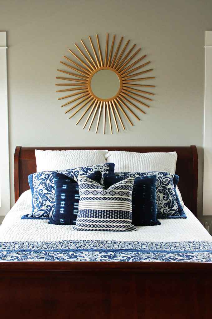 A master bedroom with dark wood furniture, white and navy bedding, and a brass sunburst mirror | modern farmhouse inspiration