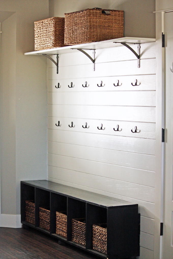A mudroom featuring a white plank wall with two rows of double coat hooks, an upper shelf with oil-rubbed bronze brackets, and a bench with storage baskets | modern farmhouse inspiration