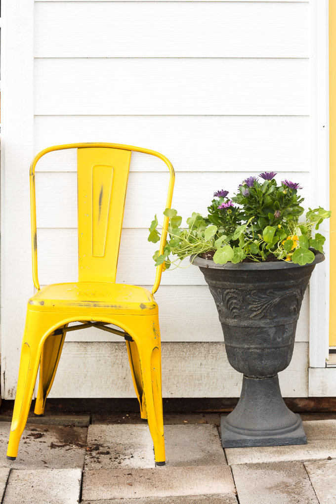 a rustic yellow chair and A chicken-friendly planter sit just outside the door of the chicken coop.