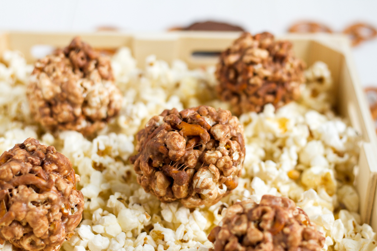 Peanut butter and pretzels fill these sweet, chocolatey popcorn balls. Make them for Halloween!
