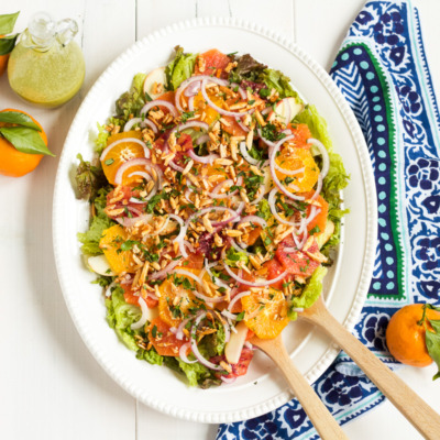 This salad is a family favorite! Tender red leaf lettuce salad is topped with thinly sliced apples, fresh oranges, red onions, and homemade sugared almonds, with an herby, from-scratch vinaigrette to top it all off.