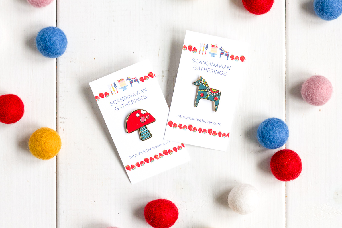 Toadstool and Dala Horse enamel pins, available from Lulu the Baker's Etsy shop