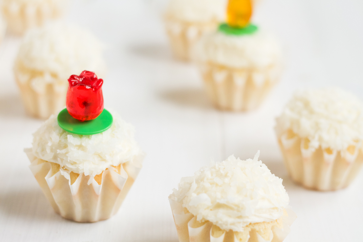 Coconut cupcakes with coconut buttercream and coconut topping, with tulip-shaped ring pops for decoration.