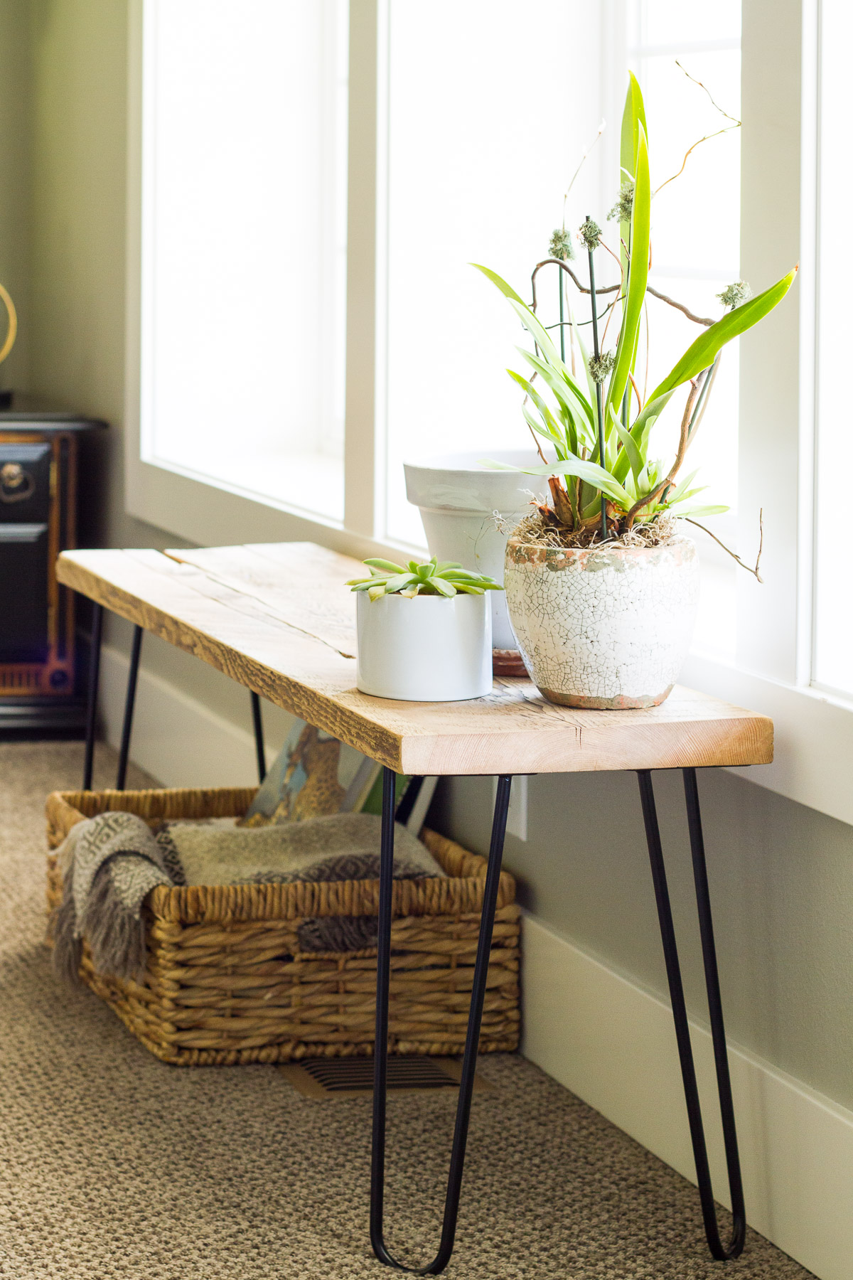 Our naturalist living room makeover included building this simple bench from hair pin legs and a leftover slab of reclaimed wood.