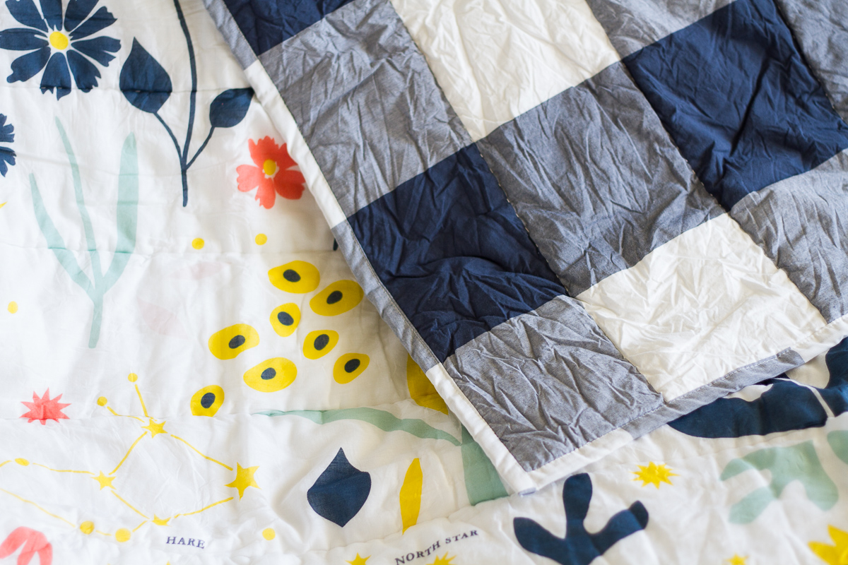 Cute bedding for a tween girl's bedroom, featuring navy buffalo check, flowers, and constellations.