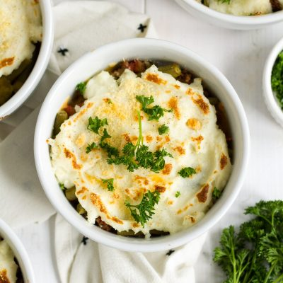 Shepherd's pie is one of my family's favorite easy dinners. These individual italian-style shepherd's pies have a delicious filling with herbs and tomatoes, and a sprinkling of parmesan cheese on top.