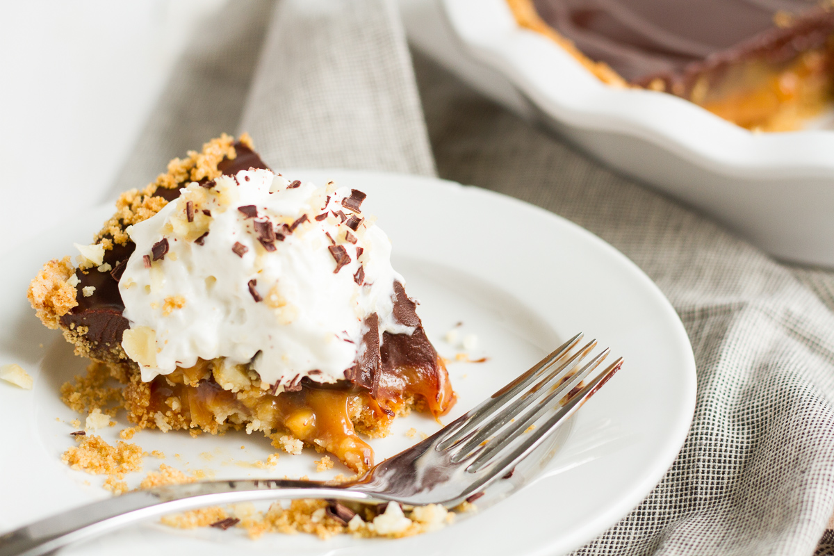 An over-the-top pie featuring a homemade graham cracker crust, a layer of macadamia nut-filled caramel, and a topping of rich chocolate ganache.
