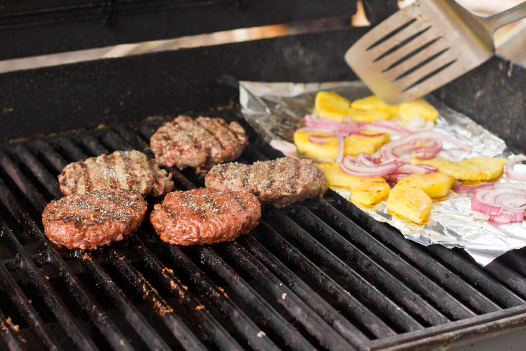 grilling beef and beyond burger patties along with pineapple and red onion slices for tropical bbq burgers