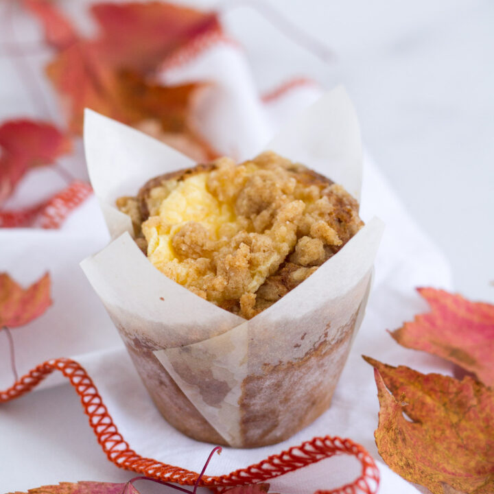pumpkin cream cheese streusel muffin on a napkin with fall leaves